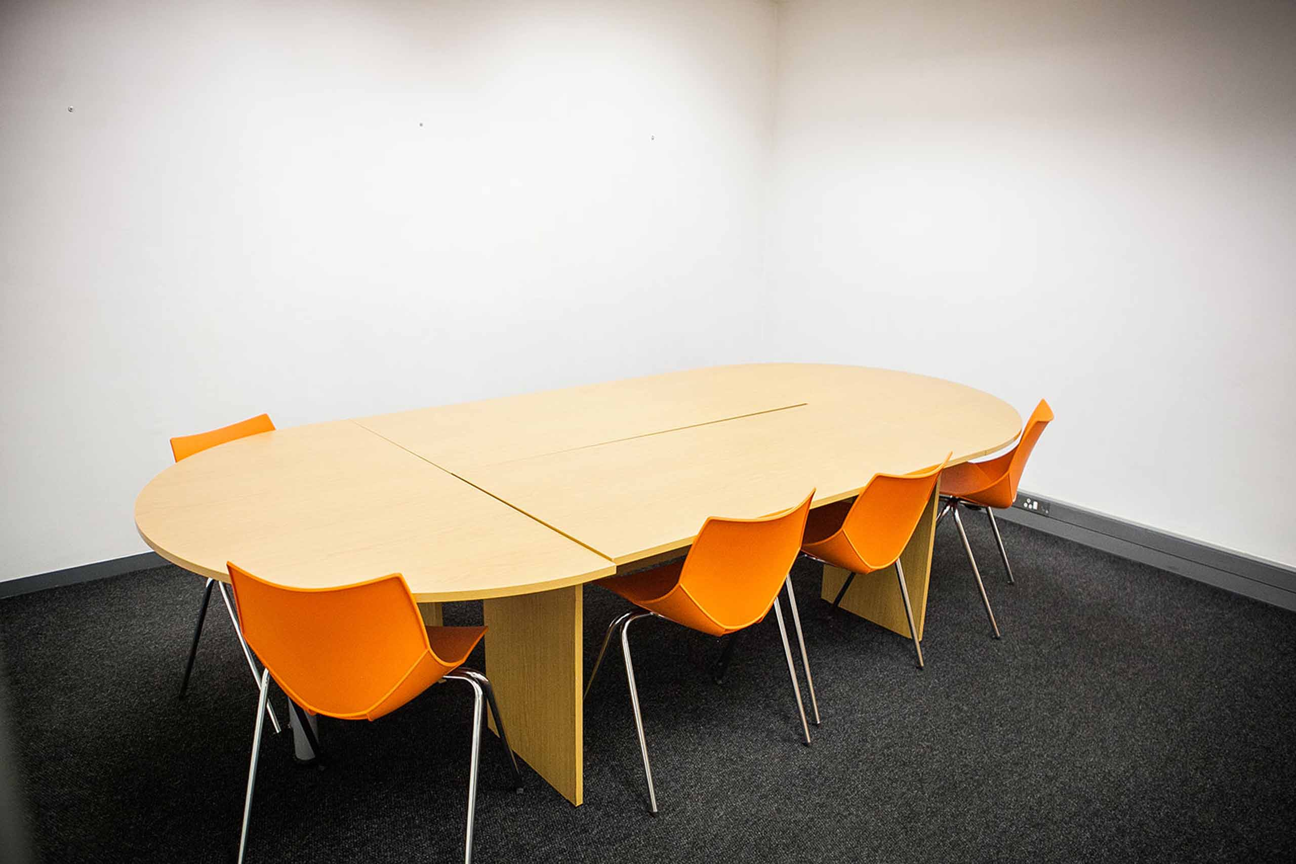 A meeting room with a modular wooden table and orange plastic chairs.