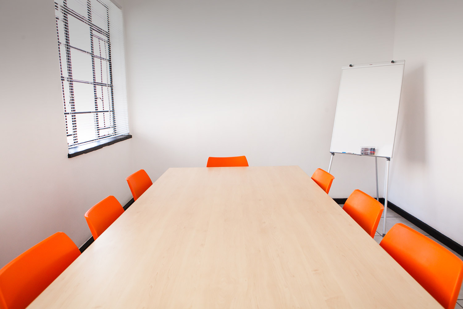 A bright XtraSpace Flexi Office meeting room with a wooden table and modern plastic orange chairs and a whiteboard.