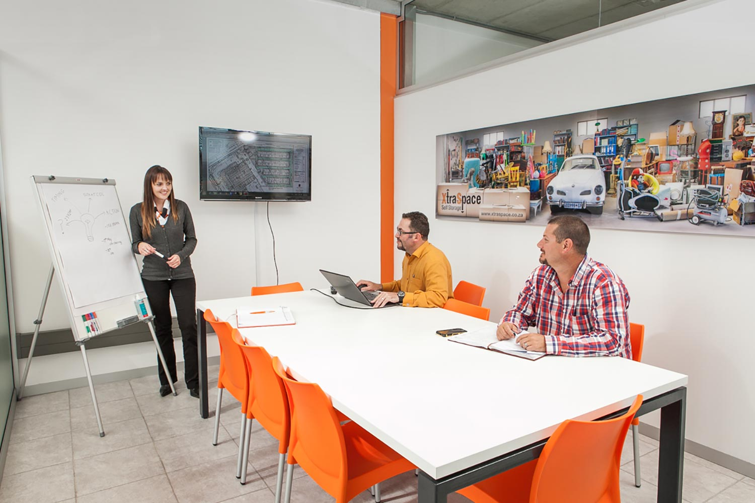 A lady presenting something to two men with the help of a whiteboard and flat screen TV inside a modern meeting room.