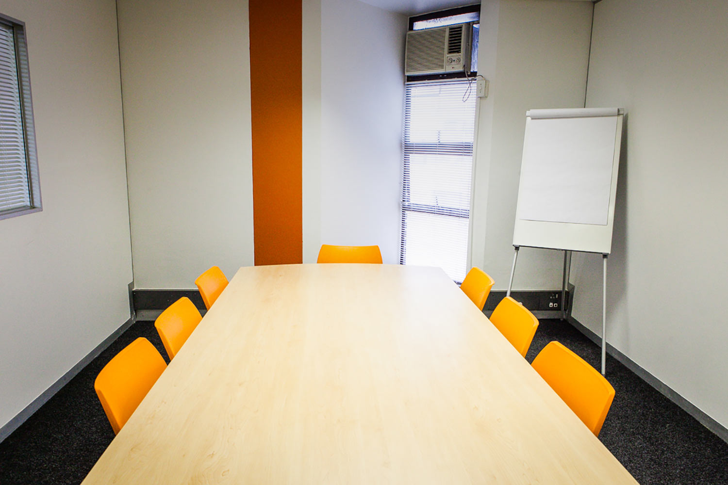 An XtraSpace Flexi Office meeting room with a wooden table and modern plastic orange chairs and airconditioning.