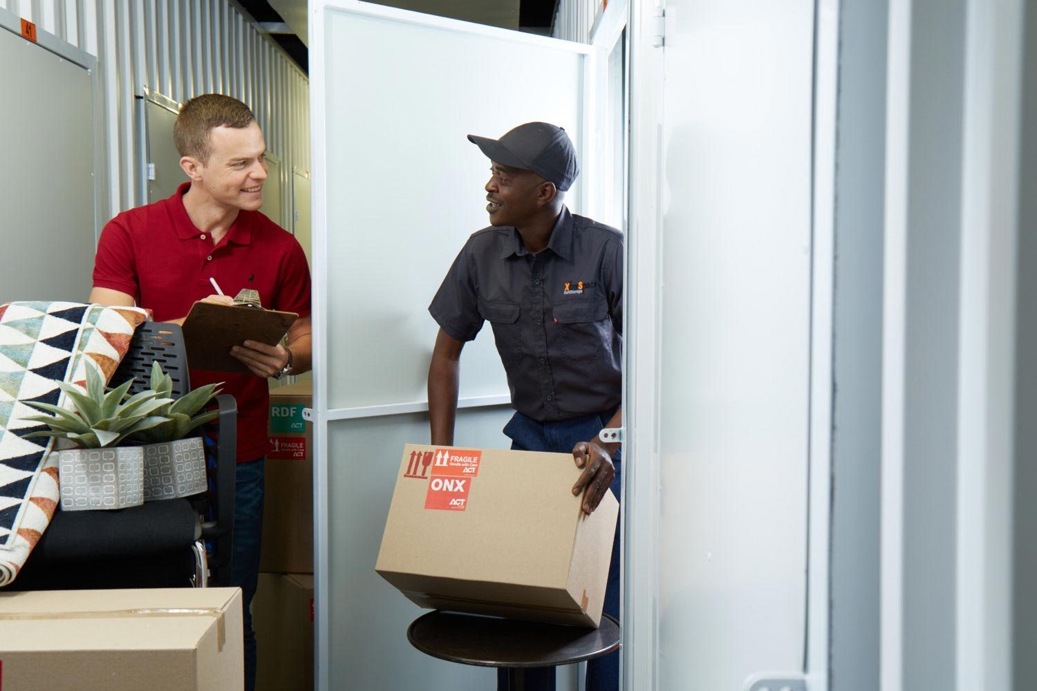 An XtraSpace employee helping a customer pack their self storage unit.