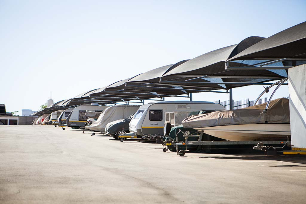 An outdoor parking yard with shaded parking bays full of boats on bot trailers and caravans.