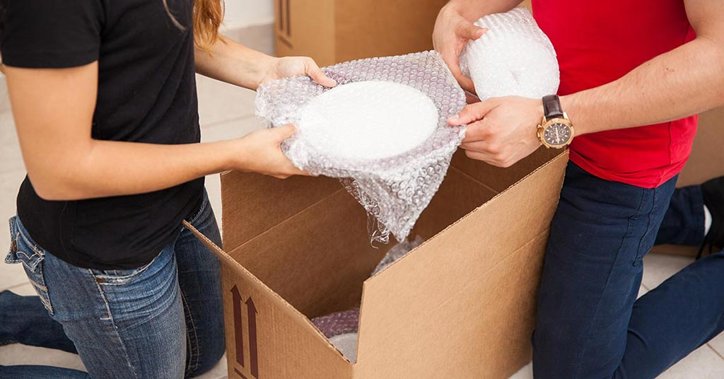 Close up of a couple packing a bubble wrapped plate into a cardboard box.