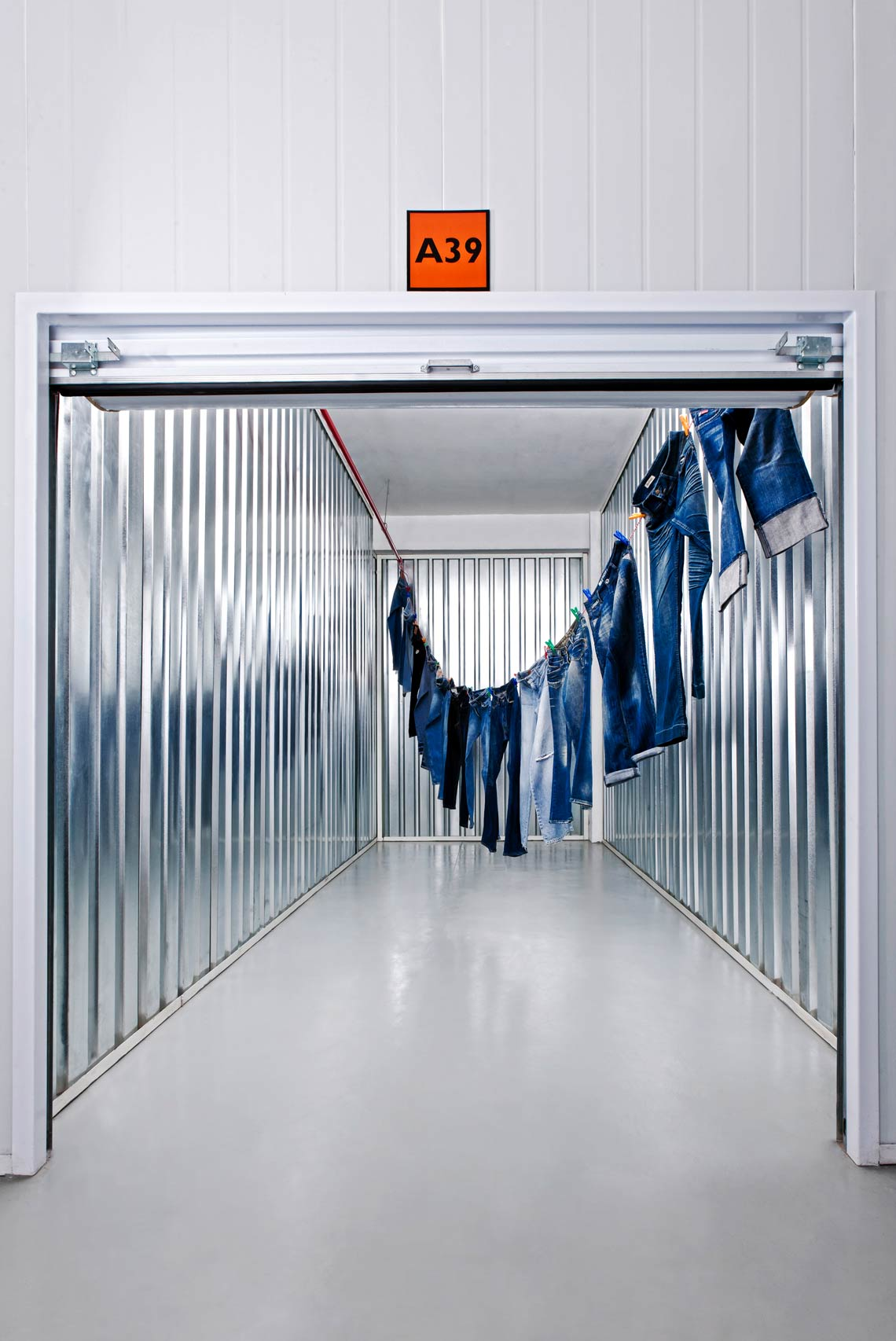 A 16 square meter storage unit spanned by a washing line full of countless pairs of jeans.