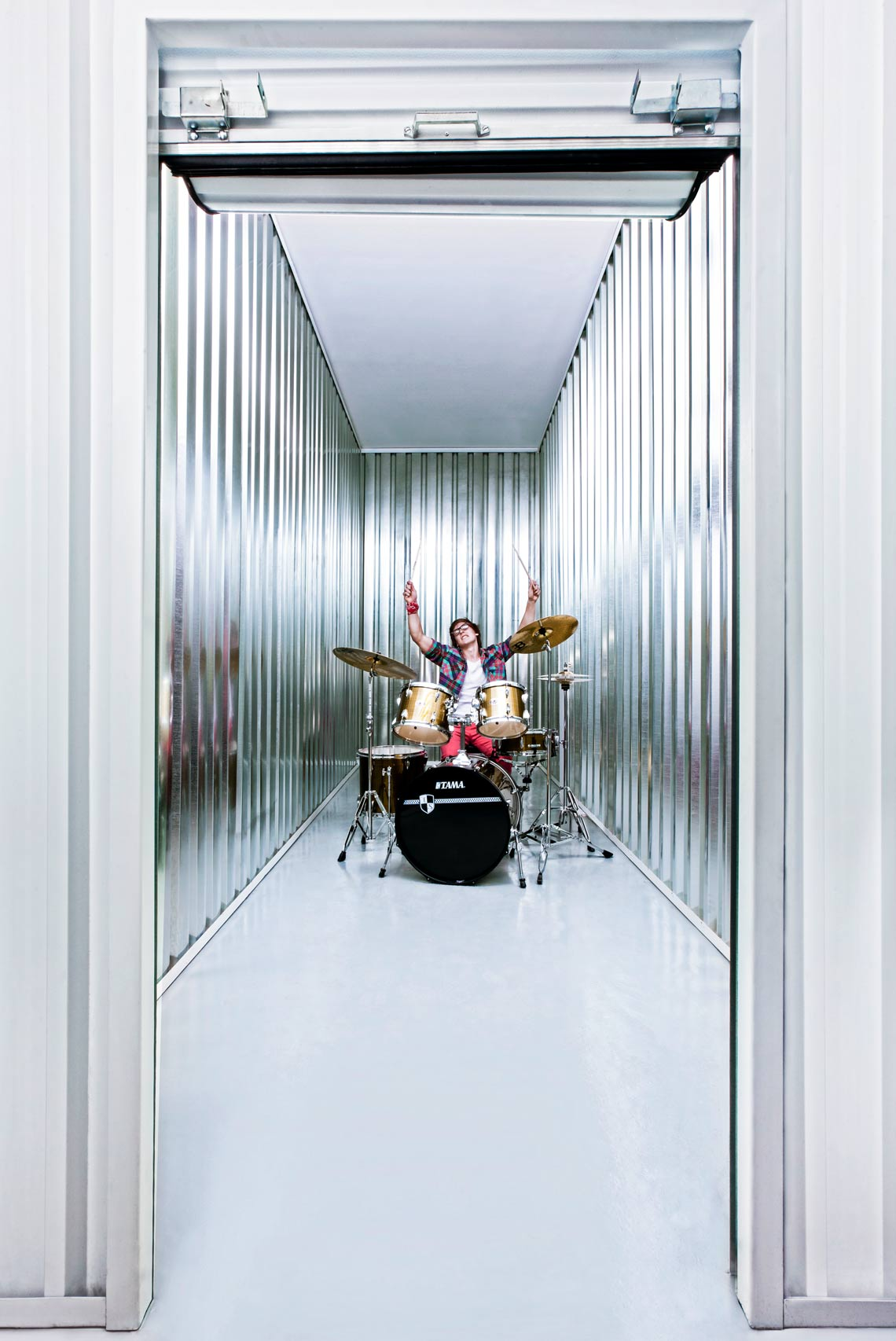 A man playing on a drumset inside a 12 square meter big self storage unit.