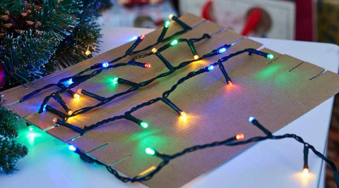 Christmas lights wrapped around a sheet of cardboard.